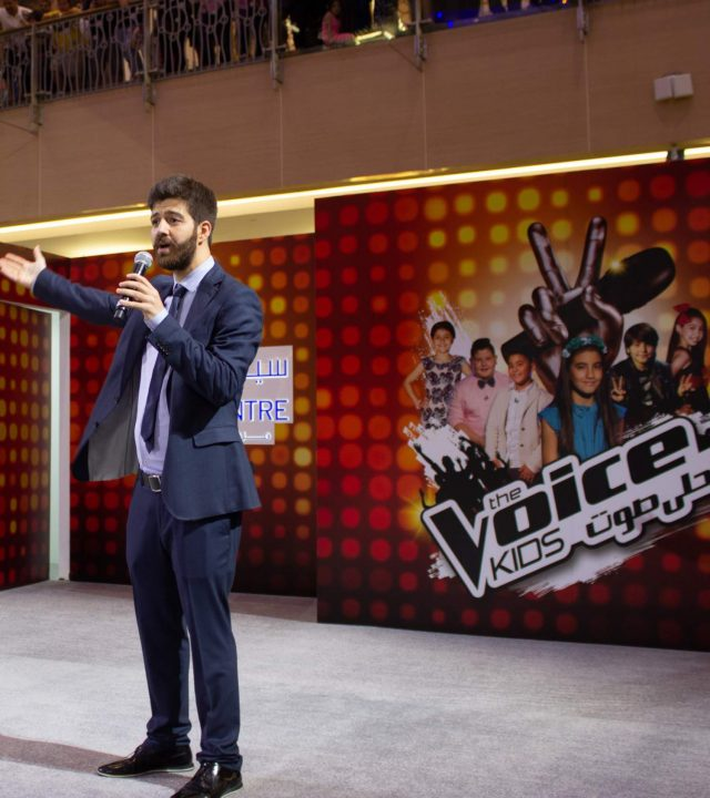 An Image with backdrop of voice arabia banner which showcases the work done by wild planet entertainment